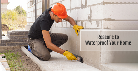 worker waterproofing the foundation of the house